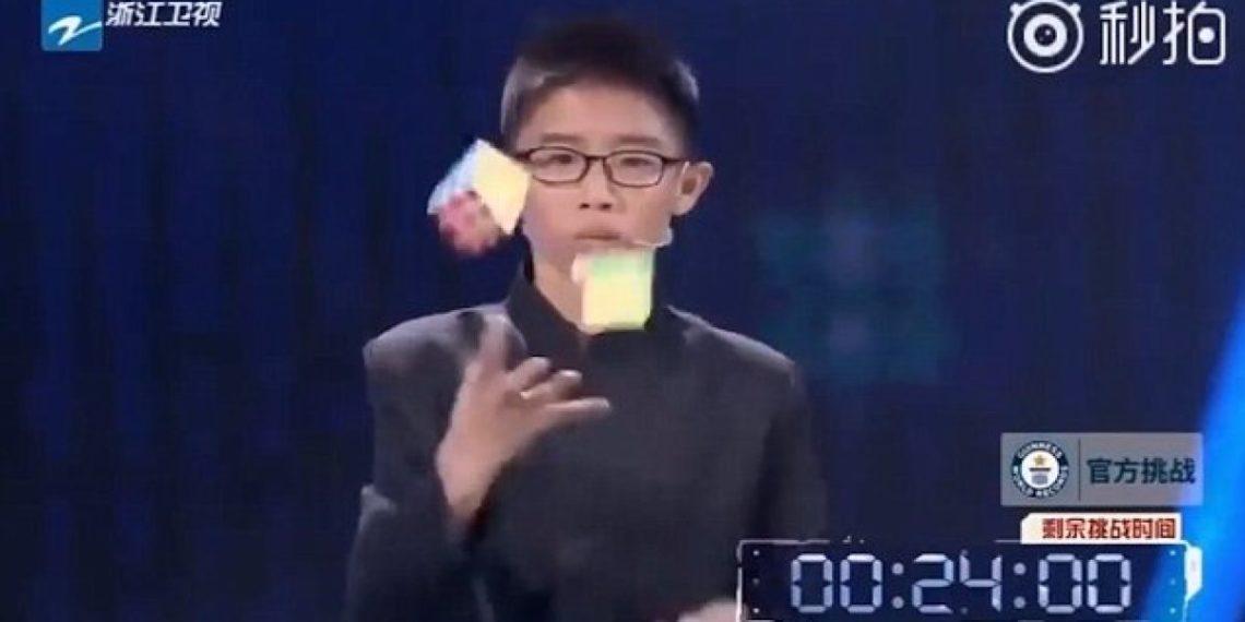 13enne cinese risolve 3 cubi di Rubik facendo il giocoliere